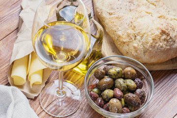 Bowl with different kind of olives, glass of wine, cheese and  fresh bread ciabatta on the wooden table.