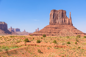 Scenic Drive on Dirt Road through Monument Valley, The famous Buttes of Navajo tribal Park, Utah - Arizona, USA. Scenic road and red rock formations.