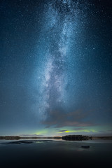 Aurora Borealis aka Northern Light above partly iced lake