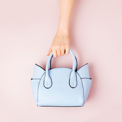 Female hands holds handbag on pink  background . Flat lay, top view. Spring fashion concept in pastel colored
