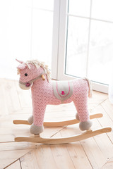 Unicorn toy horse near the window on the wooden floor