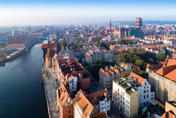 Gdansk old city in Poland. Skyline with the oldest medieval port crane (Zuraw) in Europe, St Mary church, Town hall tower, Motlawa River and bridges. Aerial view in sunrise light