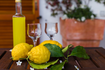 Lemonade or limoncello in a glass bottle, glasses, lemons with leaves on a serving table on the terrace