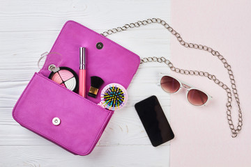 Fashion woman handbag with makeup accessories. Stylish woman essentials, cosmetics, cellphone, sunglasses on wooden background, top view.
