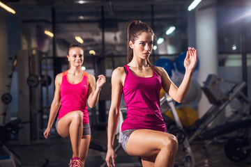 Two young energy athletic slim fitness active girls lifting legs while doing aerobics in the modern gym.