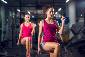Portrait close up view of two young fitness motivated attractive healthy sporty active slim girls doing exercises and warming with one raised leg in the gym.