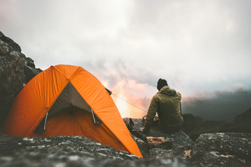 Man traveler alone enjoying sunset in mountains sitting near of tent camping gear outdoor Travel adventure lifestyle concept hiking wanderlust vacations