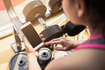 Młoda azjatykcia kobieta używa smartphone w gym