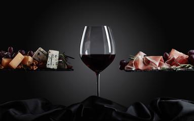 Kieliszek czerwonego wina z różnymi serami, owocami i szynką parmeńską.