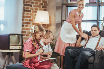 smiling parents looking at cute little kids using digital tablet, vintage style