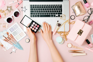 Fashion blogger working with laptop. Workspace with  female accessory, cosmetics products on pale pink table. flat lay, top view