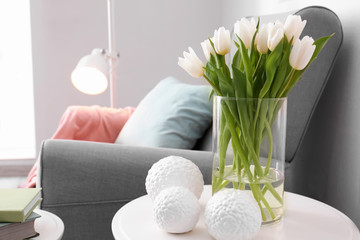 Small table with bouquet of tulips and decor in living room