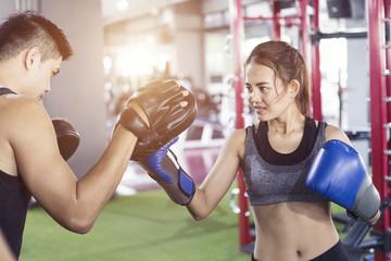 Mężczyzna trener trzymając rękawice sportowe w siłowni i kobiece rękawice. Kobieta treningu boksu w sali fitness klasy. Ćwiczenia boksu sportowego.