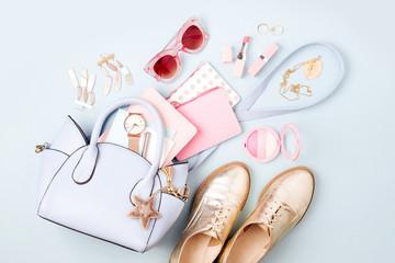 Zestaw kobiecych akcesoriów z torebką, zegarkiem, notatką, kosmetykami i butami. Leżał płasko, widok z góry. Koncepcja mody w pastelowych kolorach