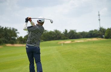 Asian man playing golf swing club for tee-off in course