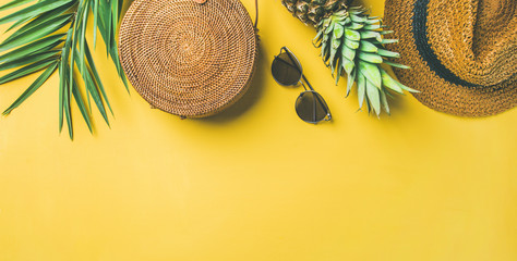 Colorful summer female fashion outfit flat-lay. Straw hat, bamboo bag, sunglasses, palm branches, pineapple over yellow background, top view, copy space, wide composition. Summer fashion, holiday