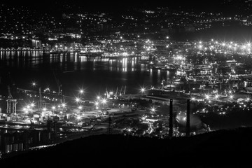 Night view of the Novorossiysk town and the bay at the Black Sea coast. Lights glow at night and make feeling of science fiction landscape.