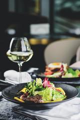 Pyszne danie mięsne z sałatką pozostawia na stole w restauracji