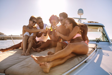 Young friends having drinks on the yacht deck