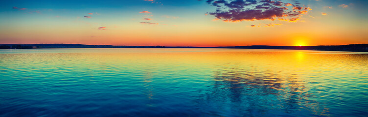 Sunset over the lake. Amazing panorama landscape