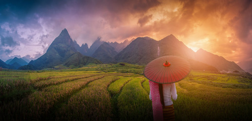 Woman holding traditional red umbrella on rice fields terraced at sunset in Sapa, Vietnam.