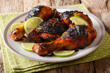 Hot spicy grilled chicken drumstick with lime and green onion close-up on a plate on a table. horizontal