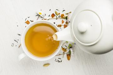 wlewając herbatę z czajniczkiem do filiżanki na białym stole