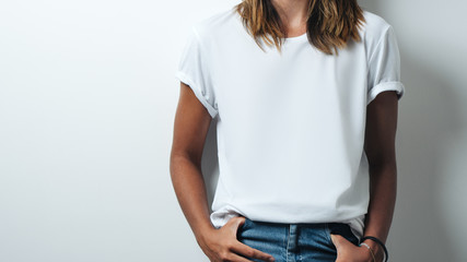 Pretty woman in white blank t-shirt, empty wall, studio close-up