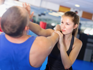 Girl and trainer are training kicks on the self-defense course