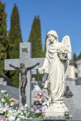 primer plano de escultura con forma de ángel colocada sobre una tumba en el  cementerio