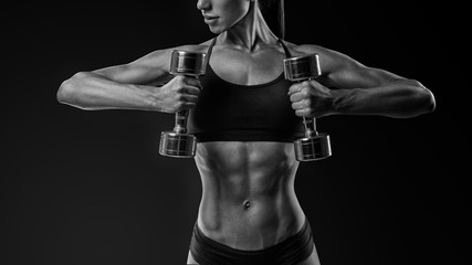 Black and white close-up shot of young female bodybuilder working out with hand weights and shorts curling dumbbell over black background Woman with muscular body, abs Clipping path
