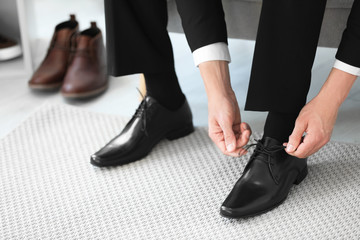 Young man trying on shoes in store