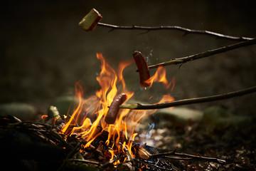 Kiełbasa pieczona nad ogniskiem w płomieniach ognia.