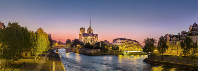 Panoramic view of Notre Dame (famous Paris landmark) along the Seine river at twilight, sunset, amazing pano with vibrant color sky