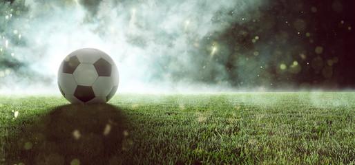 Piłka nożna leży na trawie na stadionie w dymie