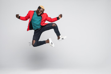 Full length portrait of a cheerful afro american man jumping isolated on a white background