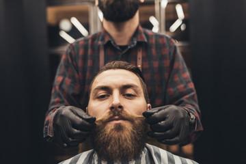 Modnisia młody przystojny mężczyzna odwiedza fryzjera męskiego sklep. Modna i stylowa broda oraz krój.