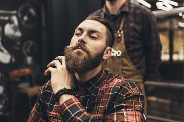 Hipster young good looking man visiting hairstylist in barber shop.