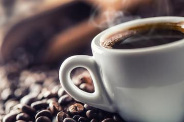 Filiżanka czarnej kawy z fasolami na drewnianym stole