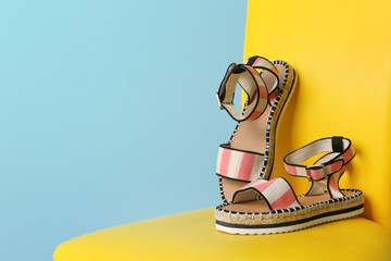 Pair of female shoes on chair against color background