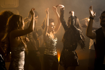 Crowd of trendy young people having fun enjoying raving nightclub party, beautiful girls dancing on dim smoky dance floor