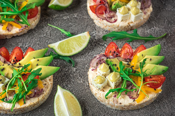 Bruschetta with tomato, avocado, herbs and arugula. Rustic background. Top view