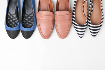 Different female shoes on white background, top view