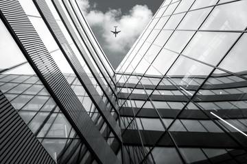 Latający samolot nad nowoczesną architekturą budynku, niski kontrast czarno-biały obraz o wysokim kontraście