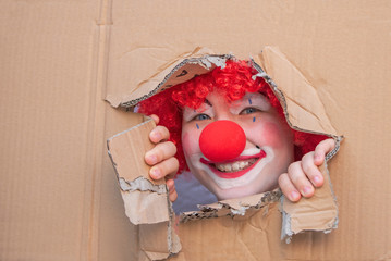 Funny kid clown with red nose playing
