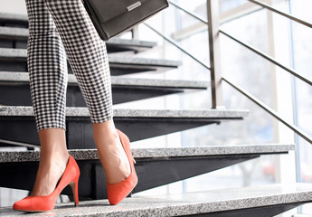 Young woman in red elegant shoes on stairs, indoors