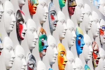 Carnival masks hanging on wall boards lie