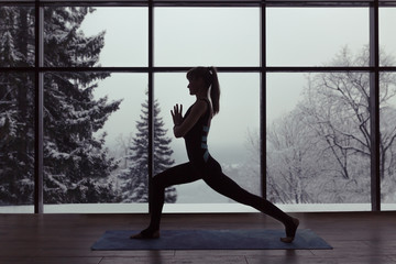 A silhouette of a woman doing yoga on background of windows with beautiful winter landscape with trees in the snow and sunlight, young yogi girl in warrior's yoga position