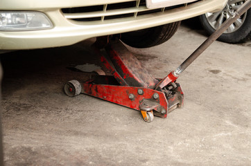 Truck lifted with old red hydraulic floor jack for engine oil replacement
