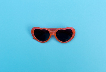 Cool sunglasses on a baby blue background, top view